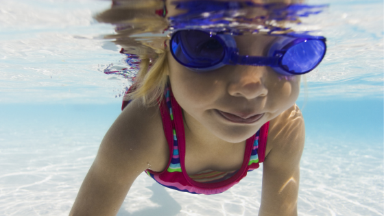 A girl wearing goggles pictured under the water