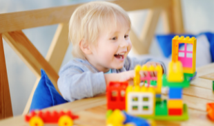 Child sitting at table playing with toys